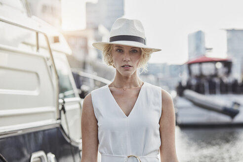 Portrait of serious young woman wearing a hat at a marina next to a yacht - RORF01560