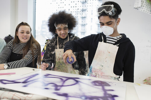 Teenagers spray painting in art class - CAIF21843