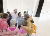 Active seniors hugging in circle - CAIF21870