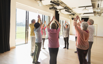 Active seniors exercising, stretching arms overhead in circle - CAIF21891