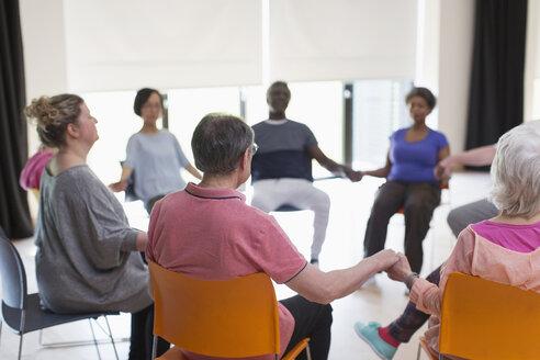 Serene active seniors holding hands, meditating in circle - CAIF21897