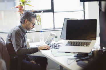 Focused businessman working at laptop in office - CAIF21948