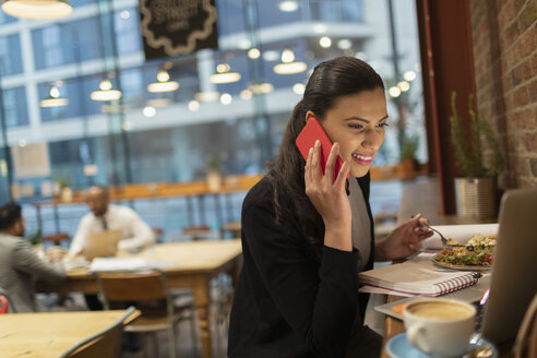 Smiling businesswoman talking on smart phone and working at laptop in cafe - CAIF21963