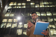 Businessman with paperwork and smart phone below urban highrise at night - CAIF21972