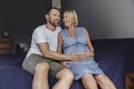 Mature man and his pregnant mature wife sitting on bed touching her belly - MFF04623