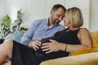 Mature man and his pregnant mature wife sitting on couch touching her belly - MFF04632