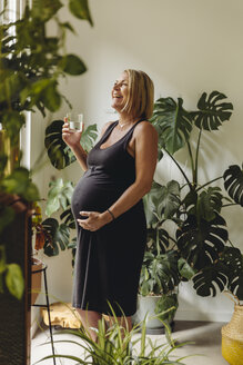 Happy mature pregnant woman having a glass of water at home - MFF04635