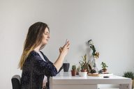 Young woman using cell phone at home surrounded by plants - AFVF01533