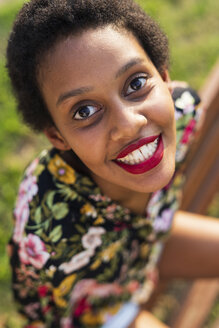 Portrait of smiling young woman sitting on bench in a park - GIOF04301
