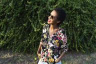 Smiling young woman wearing sunglasses and colourful blouse - GIOF04310