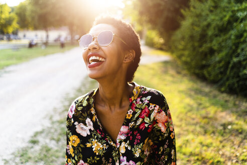 Laughing young woman wearing sunglasses outdoors at sunset - GIOF04316