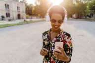 Happy fashionable young woman with headphones and smartphone outdoors at sunset - GIOF04319