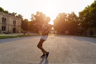 Happy fashionable young woman with headphones dancing outdoors at sunset - GIOF04322