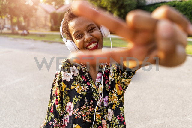 Happy fashionable young woman with headphones outdoors at sunset making victory gesture - GIOF04325