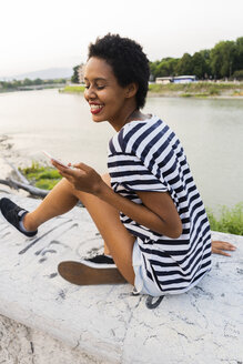Smiling young woman sitting on wall at the riverside using cell phone - GIOF04328