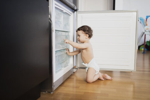 Baby boy wearing diaper exploring refrigerator in the kitchen - AZOF00003