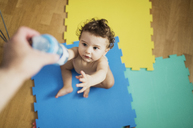 Father's hand giving baby boy a bottle of water - AZOF00006