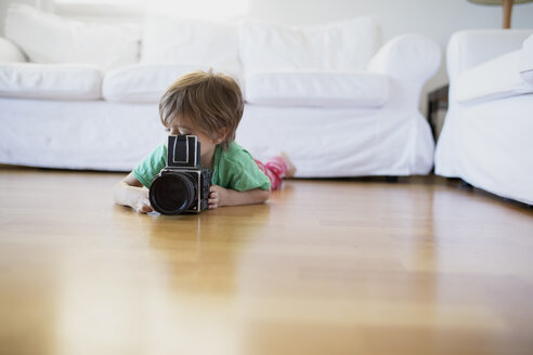 Toddler boy lying on the floor at home using an old-fashioned film camera - AZOF00015