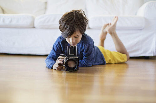 Boy lying on the floor at home using an old-fashioned film camera - AZOF00018
