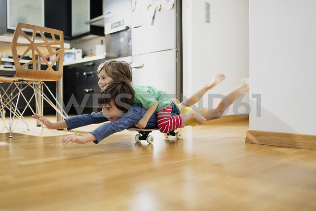 Two brothers at home lying on skateboard together having fun - AZOF00021 - Nasos Zovoilis/Westend61