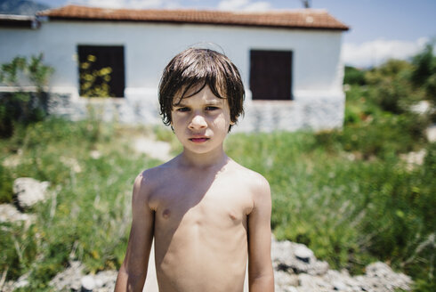 Portrait of a barechested boy standing in sunshine in front of a house - AZOF00024