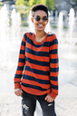 Portrait of smiling young woman wearing  sunglasses and striped pullover - GIOF04340