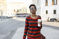 Portrait of young woman with coffee to go wearing sunglasses and striped pullover - GIOF04343