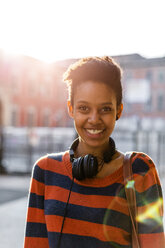 Portrait of laughing young woman with headphones at backlight - GIOF04349