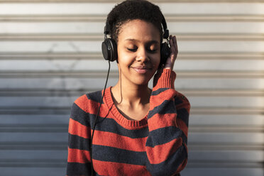 Portrait of smiling young woman  listening music with headphones - GIOF04352