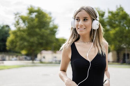 Portrait of smiling teenage girl wearing headphones - GIOF04361