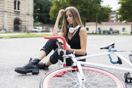 Relaxed teenage girl sitting down using cell phone next to bicycle - GIOF04364