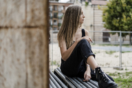 Pensive teenage girl sitting outdoors looking around - GIOF04373