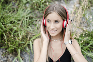 Portrait of smiling teenage girl wearing headphones - GIOF04379
