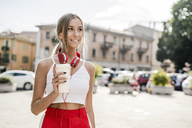 Portrait of smiling teenage girl with takeaway drink in the city - GIOF04400