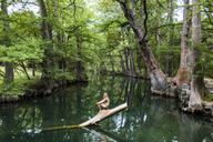 A young woman enjoys a calm swimming hole, the Blue Hole, near Wimberley, Texas. - AURF04191