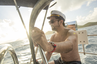 Captain steers his boat across the ocean in the British Virgin Islands. - AURF04344