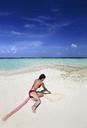 Young woman walking on sandbank beach, Maldives, Indian Ocean, Asia, Maafishi - AURF04410