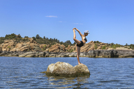 A Flexible and Athletic Young Woman Poses on a Rock in a Lake - AURF04434