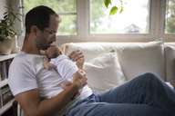 A Father Holds His Baby While Sitting At Home - AURF04440