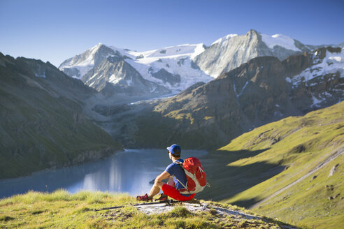 A solo male hiker enjoying the view over Lac des Dix in Val d'H├â┬®r├â┬®mence, in the Swiss Alps. - AURF04533