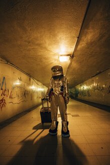 Spaceman in the city at night standing in underpass with rolling suitcase - VPIF00646