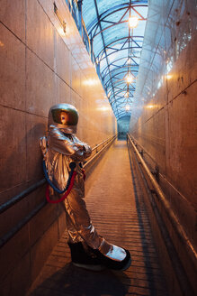 Spaceman in the city at night standing in narrow passageway - VPIF00655
