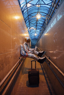 Spaceman in the city at night with rolling suitcase in narrow passageway - VPIF00658