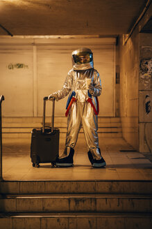 Spaceman in the city at night standing in underpass with rolling suitcase and takeaway coffee - VPIF00667