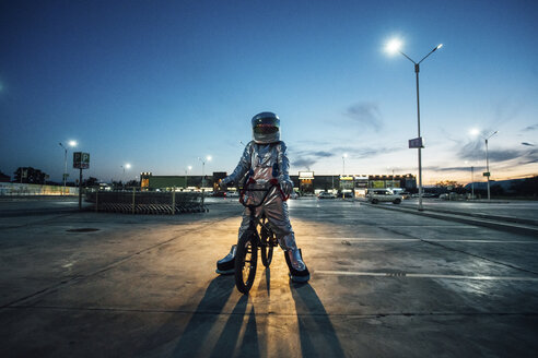 Spaceman in the city at night on parking lot with bmx bike - VPIF00670