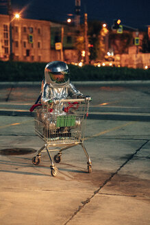 Spaceman in the city at night on parking lot inside shopping cart - VPIF00679