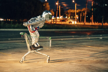Spaceman in the city at night on parking lot inside shopping cart - VPIF00682