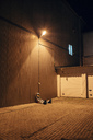 Spaceman sitting under lamp at a wall at night - VPIF00697