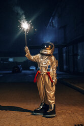 Spaceman standing outdoors at night holding sparkler - VPIF00700