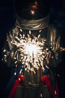 Spaceman standing outdoors at night holding sparkler - VPIF00703